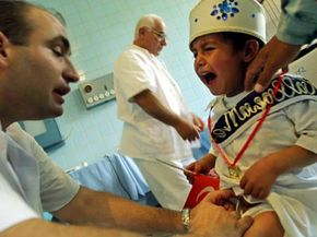 A little boy cries as a Turkish doctor injects him with a local anesthetic before circumcising him in Kabul, Afghanistan.