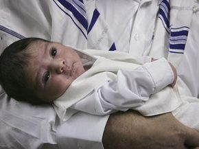Shalom Hen, the father of eight-day-old Ofir Hen, holds his child during a circumcision ceremony by the local rabbi inside a bomb shelter on July 26, 2006, in Haifa, Israel.