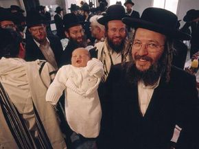 A Jewish man proudly shows off a boy after a circumcision in April 2001 in Jerusalem.