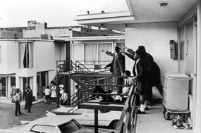 Civil rights leader Andrew Young and others standing on balcony of the Lorraine Motel in Memphis, Tenn., pointing in the direction of the assailant after the assassination of civil rights leader Martin Luther King Jr., who is lying at their feet.