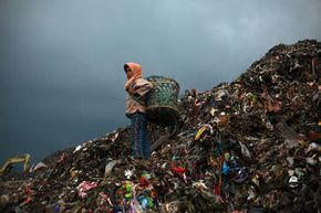 Scavenging for plastic, a child stands atop a mountain of garbage in one of Indonesia's largest dump sites.