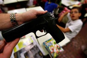 A police officer shows a toy gun next to a student during the Weapon is not a Toy campaign at Joao Deus Cardoso school in Sao Paulo, Brazil.