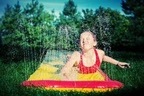 A girl enjoys the Slip 'N Slide on a sunny day. This is one toy best left to children -- unles you want to make one with an extremely long slide.