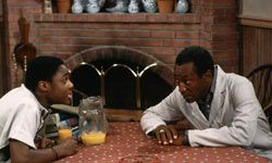 """Theo and Cliff share some family time around the uncluttered kitchen table of """"The Cosby Show."""""""