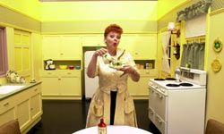 """A Lucy Ricardo impersonator strikes a pose in a recreation of the impossibly clean kitchen set of """"I Love Lucy"""" during an exhibition celebrating the 50th anniversary of the TV sitcom."""