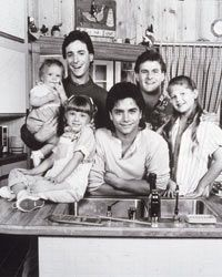 """A very early shot of the """"Full House"""" cast -- check out baby Mary-Kate or Ashley Olsen -- in their kitchen.  Somehow 3 bachelors and 3 little girls managed to keep that place spotless!"""