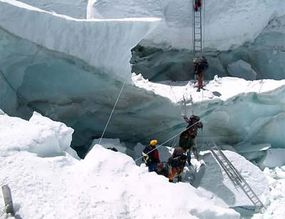 Climbers using ropes and ladders to traverse the Khumbu Icefall.