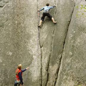 The type of climbing pictured above, in which the climber is using ropes and hooks, is classified as aid climbing.