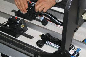 The balsa wood cars are attached to a thin wire on the track by hooks attached to the car. The C02 canisters are fired with a special device that punctures a hole in the canister when a computer instructs it to do so. This allows a fair race.