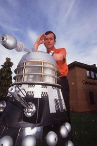 Professor Kevin Warwick poses on a Dalek and holds a tiny RF chip he had surgically implanted in his arm.