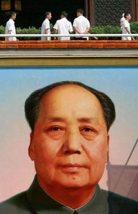 Chinese plainclothes paramilitary police officers patrol above the huge portrait of late communist leader Mao Zedong displayed at the Tiananmen Gate in Beijing.