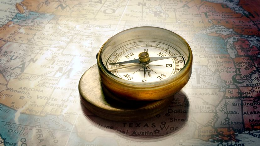 Gold Compass Resting on Map