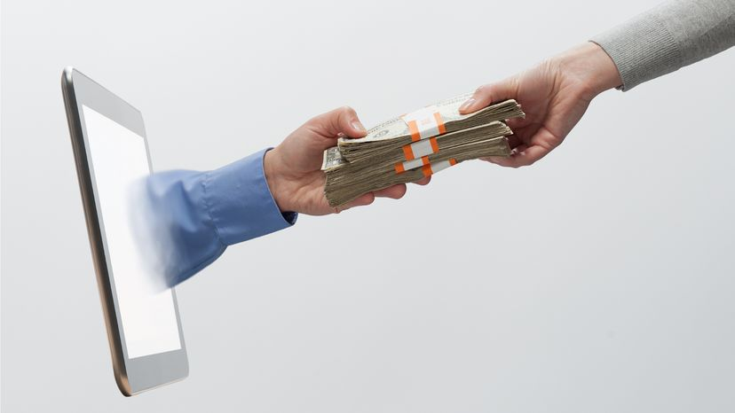 Woman's hand, handing employee compensation money to mans hand coming from digital tablet