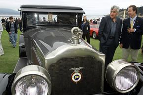 Comedian Jay Leno (second from right), looks over a 1925 Packard 236 on display during the Pebble Beach Concours d'Elegance in Pebble Beach, Calif.