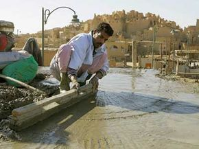 Concrete roofs aren't necessarily a costly investment. Here, an Egyptian worker levels concrete on the roof of a new building close to the ruins of the ancient fortification of Shali.