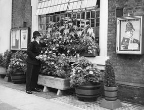 A policeman tends the window boxes at the front of Gerald Road Police Station in London.