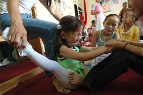 This little girl is not very happy about contortion training  at the Mongolian Circus School. Mongolia is famous for its contortionists who usually start at very young ages.