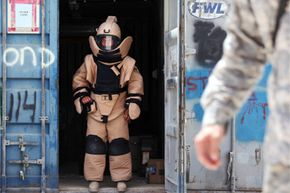 A member of a U.S. Army Explosive Ordnance Disposal (EOD) team stands at the entrance to a container before an exercise in Kandahar City, Afghanistan, on June 15, 2010.