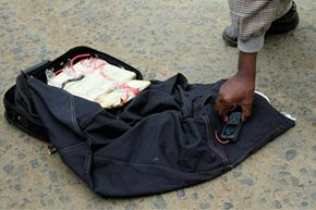 A police officer handles a defused improvised explosive device that was found in a public bus in Nairobi, Kenya on March 31, 2013. The IED was ready for detonation when the 25-sitter mini-bus crew discovered it wrapped in a bag, witnesses said.