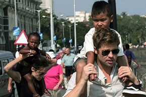 Brad Pitt carries adopted son Maddox as Angelina Jolie carries adopted daughter Zahara during a 2006 stay in India. Safe to say that the power couple knows a thing or two about adoption and its costs.