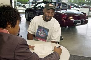 A sales representative explains a leasing contract to a customer at the Bob Maxey Ford dealership in Detroit.