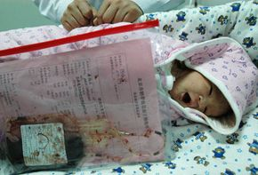 A newborn baby boy lies on a bed beside a bag of umbilical cord blood collected from him at Beijing Chuiyangliu Hospital on March 8, 2005, in Beijing. See more pregnancy pictures.