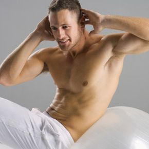 This runner is strengthening his core muscles by doing crunches on a stability ball.