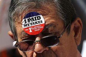 A protestor wears stickers on his face during a Tax Day demonstration in New York City. Dozens of protesters demonstrated against loopholes that allow banks and corporations to pay lower income taxes than most individual filers.