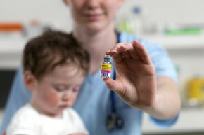 Pediatrician with a vial of MMR vaccine and a 15-month-old boy. In the U.S., the Advisory Committee on Immunization Practices recommends a two-dose vaccine schedule for measles, mumps, rubella vaccines for children, with the first dose at age 12-15 months and the second at age 4-6 years.