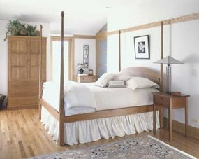 A simple, pencil-post bed in Craftsman style recalls the pristine qualities of even earlier Shaker style. The fretwork on the oak armoire is a key Craftsman characteristic, as is the geometric form of the bedside lamp.