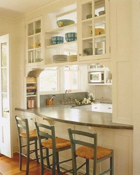A sweep of curved stone, something you would never have seen in the olden days, makes a pleasing, dramatic countertop for a pass-through. White, traditional cabinets and rush-seated stools add warmth.