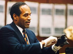 O.J. Simpson tries on a leather glove allegedly used in the murders of Nicole Brown Simpson and Ronald Goldman during testimony in his murder trial June 15, 1995, in Los Angeles.