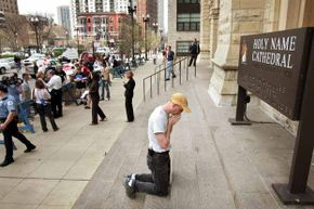 Mark Zak kneels to pray outside Holy Name Cathedral in Chicago during a demonstration calling for Cardinal Francis George to resign following his failure to take immediate action a priest charged of sexually abusing three boys.