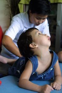 A Thai child with cerebral palsy reacts as massage is applied to her back to alleviate a muscle spasm at a treatment center in Bangkok, Thailand.