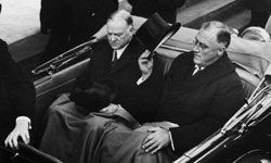 President Franklin D. Roosevelt tips his hat while sitting in the back of a car with former President Herbert Hoover at the inauguration Janurary 1933 in Washington, D.C.