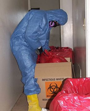 This worker is packaging biohazardous waste for transport.