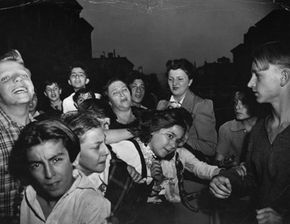 """Weegee's famous photograph """"Their First Murder"""" shows a crowd with mixed emotions gathered after a murder in Williamsburg in New York City."""