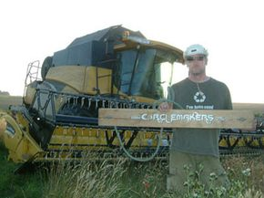 Circlemaker John Lundberg displaying one of the 'stalk stompers' (and standing in front of the combine) his team will use to create the formation.