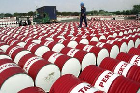 An Indonesian worker walks on barrels of oil at a distribution station of the state-owned oil company Pertamina in Jakarta, Indonesia, on June 24, 2005. See more oil field pictures.