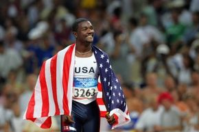 Justin Gatlin celebrates after winning the gold at the 2004 Olympics. Seven years later, he'd experience some nasty cryotherapy-induced skin problems.