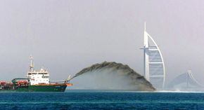 A dredger pumps sand to form a palm-shaped island