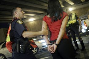 Police arrest a woman after she failed a field sobriety test at a DUI checkpoint.