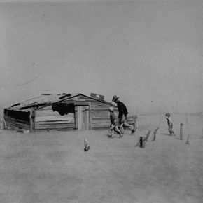 A father and son are slowed by a dust storm in their walk toward a shack.