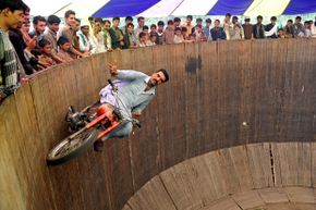 As if riding a motorcycle on a wall weren't risky enough, this bold performer decided to take his hands off the handles.
