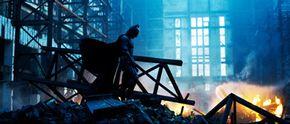 "Christain Bale as ""Batman"" walks above some debris."