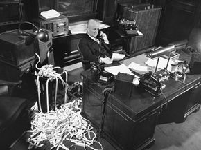 Stockbroker Gerald M. Loeb of the firm Hutton & Co. talks on the phone as ticker tape comes pouring in.