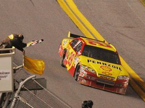 NASCAR driver Kevin Harvick crosses the finish line as the checkered and yellow flag are waved to win the NASCAR Bud Shootout Saturday, Feb. 7, 2009 in Daytona Beach, Fla.