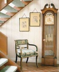 A set of antique prints complement the handsome grandfather clock.