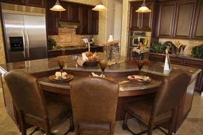 These comfortable leather chairs and the warm colors of the kitchen entice the family around the island to spend time and dine.