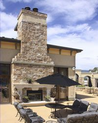 Despite the large chimney, the fireplace harmonizes with the outdoor seating.